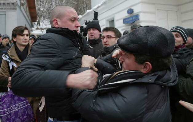 Opposition leader Sergei Udaltsov, left, fights with some of supporters of another opposition leader Eduard Limono, unseen, as he comes to pay his last respects to Alexander Dolmatov during mourning ceremony in Moscow, Russia, Wednesday. Relatives held funeral services Monday for Alexander Dolmatov, 36, who Dutch authorities say killed himself in a Rotterdam asylum deportation center last month. The Russian opposition activist who committed suicide has been laid to rest amid ongoing controversy over his treatment from the Dutch asylum system. Photo: AP