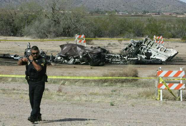 Casa Grande Police sgt. Francisco Lujan talks on the phone at the site of a plane crash that killed two people Wednesday at Casa Grande Municipal Airport in Casa Grande, Ariz.  Federal Aviation Administration officials say the twin-engine turbo prop went down at 11:35 a.m. Wednesday as it was landing and the craft was destroyed by fire. FAA spokesman Ian Gregor says the cause of the crash is unclear. He says an FAA investigator is en route to the scene. Casa Grande police and fire officials didn't immediately release the names of the two killed. Photo: AP