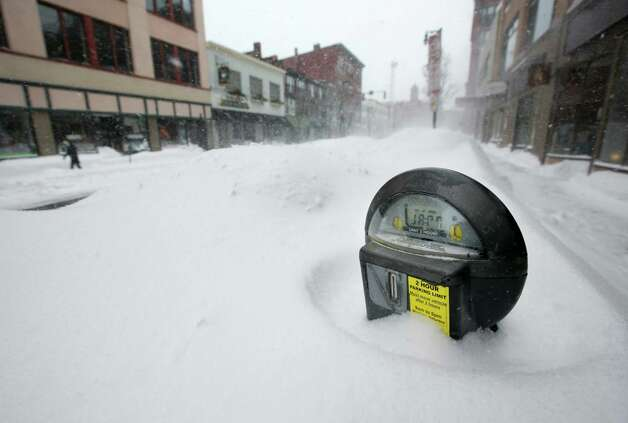 A parking meter pokes out of a snow bank during a blizzard, Saturdayin Portland, Maine. The storm dumped more than 30 inches of snow as of Saturday afternoon, breaking the record for the biggest storm on record. Photo: AP