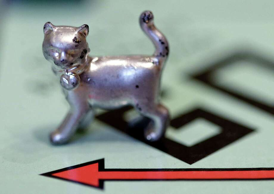 The newest Monopoly token, a cat, rests on the game board at Hasbro Inc. headquarters, in Pawtucket, R.I., Tuesday. Voting on Facebook determined that the cat would replace the iron token. Photo: AP