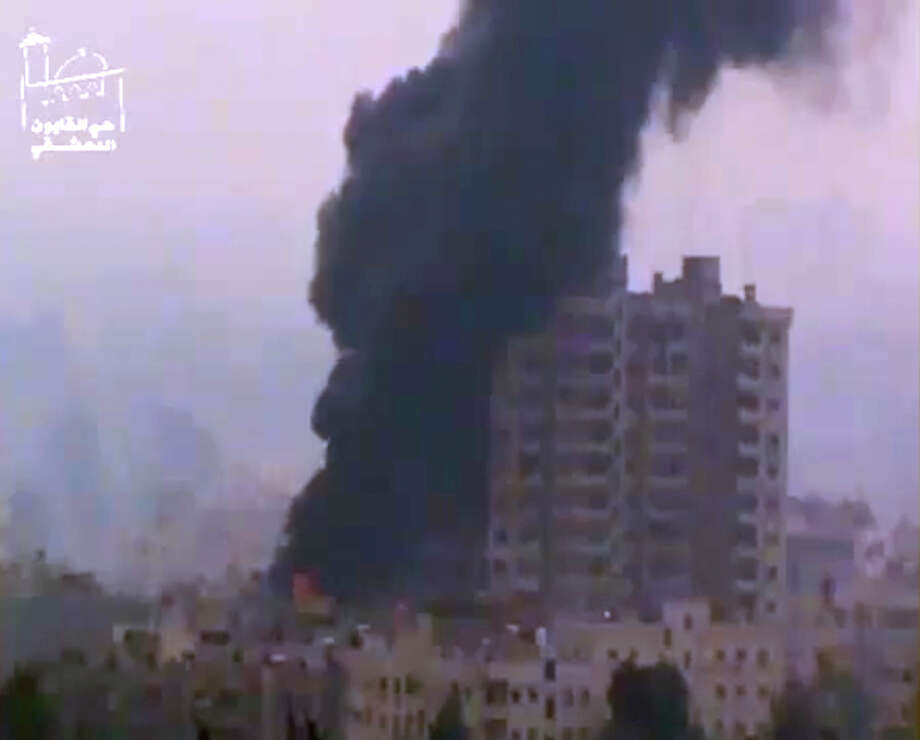 This image taken from video obtained from Ugarit News, which has been authenticated based on its contents and other AP reporting, shows smoke and fire billowing from an explosion in Damascus, Syria, Wednesday. Heavy fighting erupted in Damascus Wednesday as government forces tried to hold back a new rebel effort to push the civil war into the heart of the Syrian capital, activists said. Photo: AP