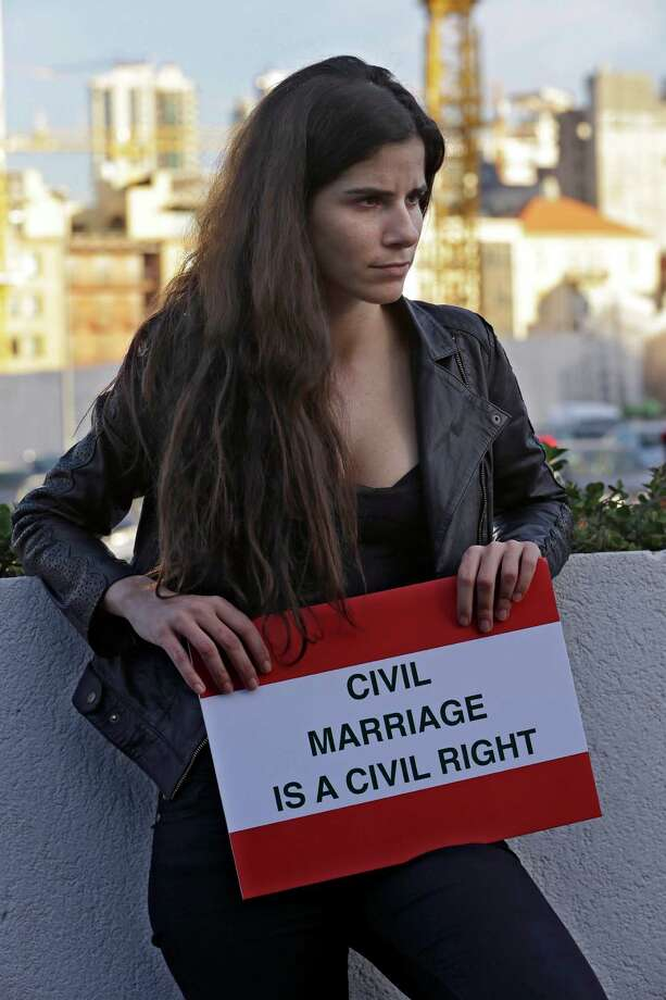 "A Lebanese woman holds a placard as she attends a protest demanding a law that guarantees any Lebanese citizen the right to a civil marriage, in Beirut, Lebanon, Monday. Last week, Lebanon's top Sunni cleric, Grand Mufti Mohammed Rashid Kabbani, fired back, blasting the effort to ""plant the germ of civil marriage in Lebanon"" with a religious edict declaring any Muslim official who participated in its legalization an ""apostate."" Christian leaders have been less outspoken, although they have opposed such laws in the past. Photo: AP"