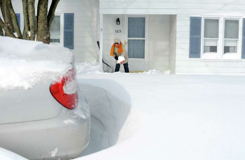 A residents on Burroughs Rd. shovels her entrance after a overnight blizzard dumped over two feet of