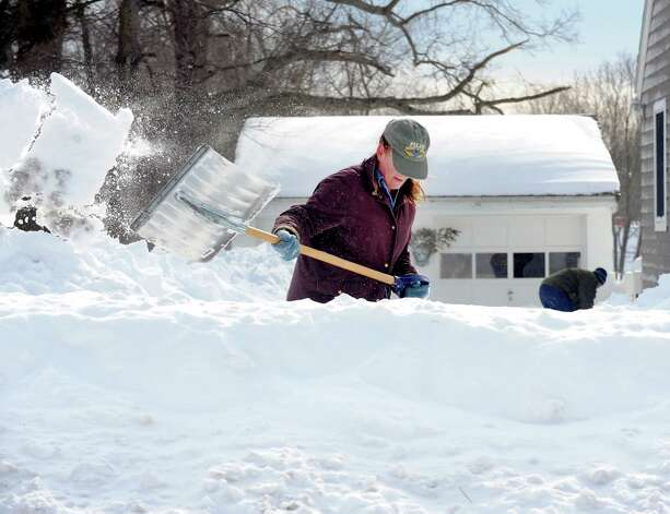 Sandra Pederzini  and her husband Matthew Fiedler shovel their driveway on Judd St. in Fairfield, Conn. on Saturday, Feb. 9, 2013. Southwestern Connecticut was hit by one of the biggest snowstorms in history, a howling blizzard that dumped up to three feet of snow across the state. Photo: Cathy Zuraw / Connecticut Post