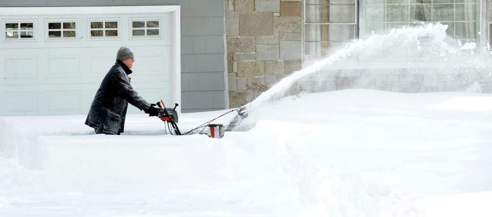 A resident on High Street clears his driveway after a overnight blizzard dumped over two feet of sno