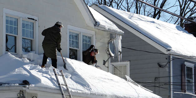 Tom and Sally Landry shovel snow off a sunroom roof at their Smith Street home Sunday morning in advance of rain expected Monday.  FAIRFIELD CITIZEN, CT 2/10/13 Photo: Mike Lauterborn / Fairfield Citizen contributed