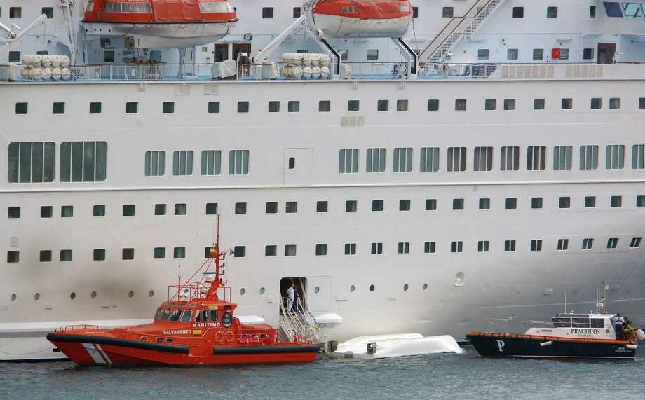 An orange rescue boat docks by a capsized lifeboat from the British-operated cruise ship Thomson Majesty in Santa Cruz port of the Canary Island of La Palma, Spain, on Sunday. A lifeboat from the Thomson Majesty fell into the sea at port in Spain's Canary Islands, killing five people and injuring three others Sunday, officials said. Rescue personnel were called to the dockside after a lifeboat with occupants had fallen overboard from a cruise ship. Spanish national broadcaster RTVE said an emergency training drill was taking place at the time of the accident. Photo: AP