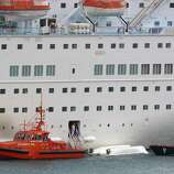 An orange rescue boat docks by a capsized lifeboat from the British-operated cruise ship Thomson Majesty in Santa Cruz port of the Canary Island of La Palma, Spain, on Sunday. A lifeboat from the Thomson Majesty fell into the sea at port in Spain's Canary Islands, killing five people and injuring three others Sunday, officials said. Rescue personnel were called to the dockside after a lifeboat with occupants had fallen overboard from a cruise ship. Spanish national broadcaster RTVE said an emergency training drill was taking place at the time of the accident.