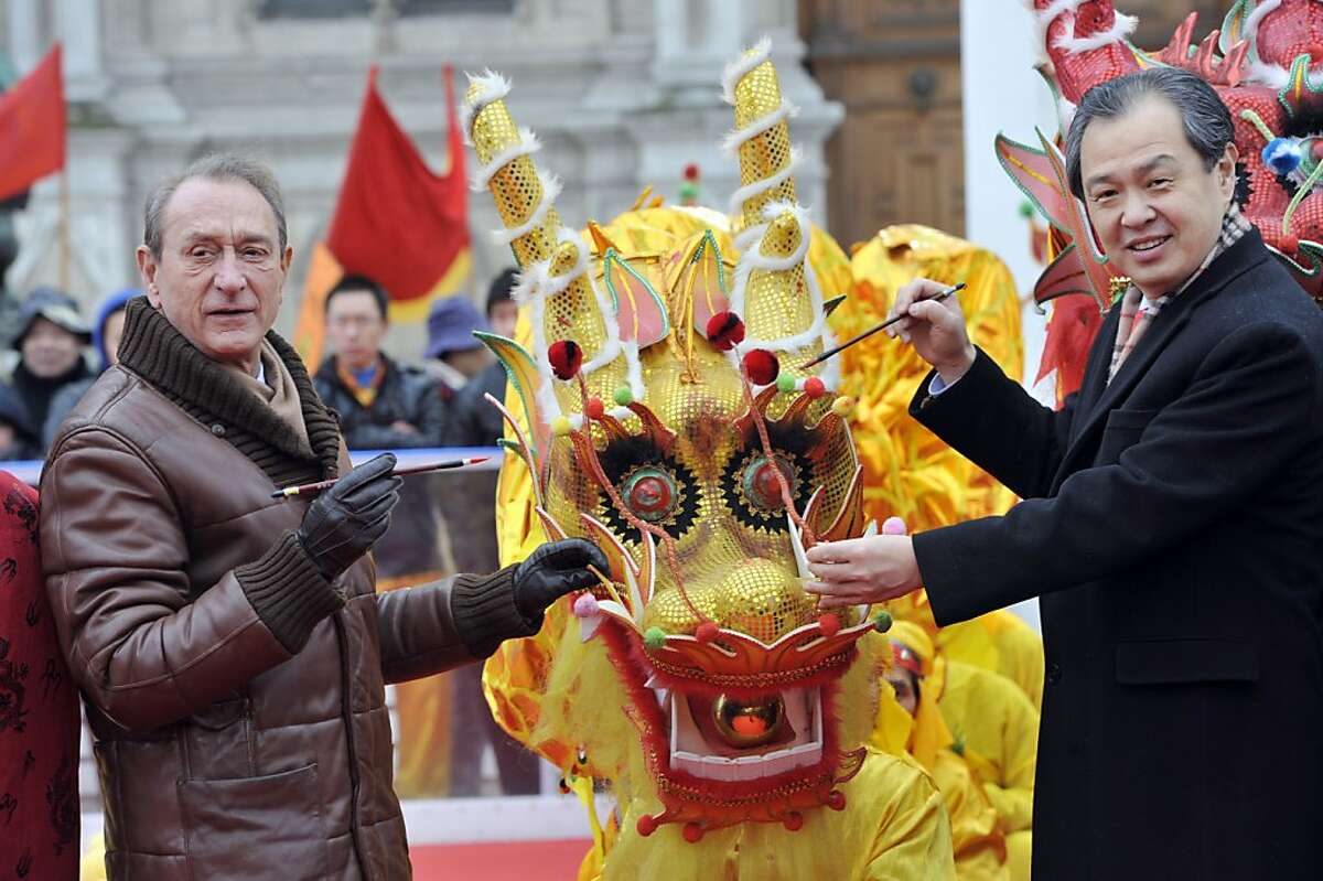 Paris Mayor Bertrand Delanoe (left) and China's ambassador in France Kong Quan traditionally paint the eye of a dragon in front of Paris City Hall during the Chinese New Year celebrations on February 10, 2013 in Paris. Chinese communities world wide traditionally welcomed in the 'Year of the Snake'.