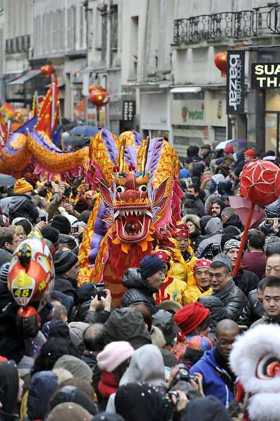 Performers surrounded by the crowd hold a dragon as they dance during a parade in Paris on February