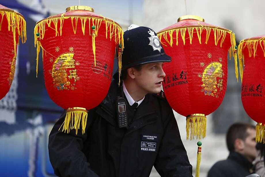 A British police officer peers through lanterns as performers in Trafalgar Square celebrate Chinese New Year in London on February 10, 2013. Chinese communities world wide traditionally welcomed in the 'Year of the Snake'. Photo: Justin Tallis, AFP/Getty Images