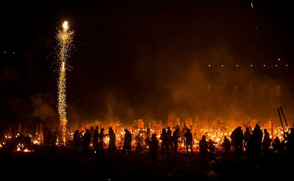 Chinese people light fireworks and burn incense at Dafo Temple in the Lunar new year celebrations in