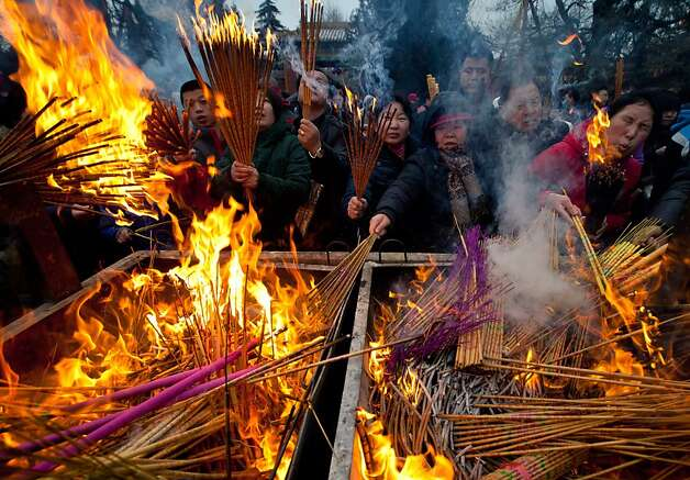 Temple-goers burn incense as they pray for health and fortune on the first day of the Chinese Lunar New Year of the Snake at Yonghegong Lama Temple in Beijing. Photo: Andy Wong, Associated Press