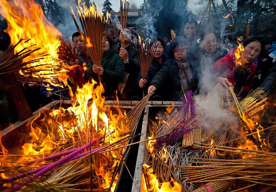 Temple goers burn incense as they pray for health and fortune on the first day of the Chinese Lunar New Year at Yonghegong Lama Temple in Beijing Sunday, Feb. 10, 2013. Millions across China are celebrating the arrival of the Lunar New Year, the Year of the Snake, marked with a week-long Spring Festival holiday. Photo: Andy Wong, Associated Press