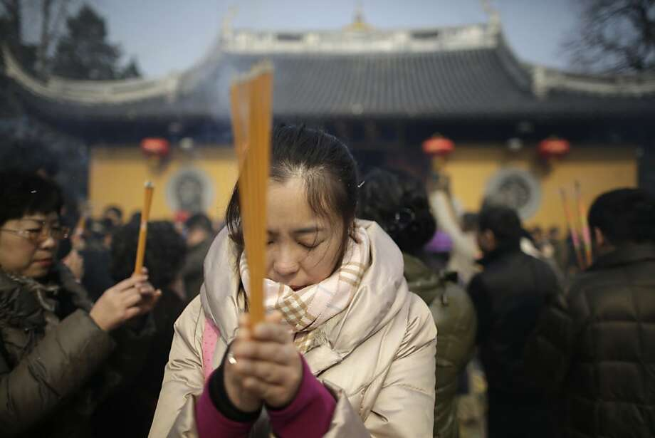 A woman burns joss sticks while praying at Longhua Temple on the first day of the Lunar New Year in Shanghai, China on Sunday, Feb. 10, 2013.  Millions across China are celebrating the arrival of the Lunar New Year, the Year of the Snake, marked with a week-long Spring Festival holiday. Photo: Eugene Hoshiko, Associated Press