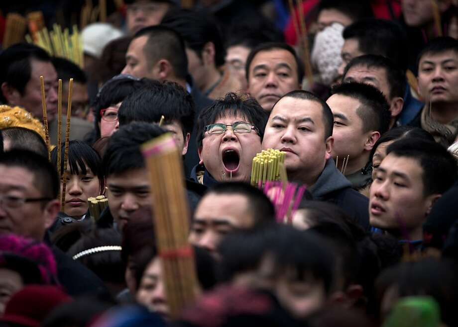A Chinese man, center, yawns as he and other worshippers gather to pray on the first day of Chinese Lunar New Year at Yonghegong Lama Temple in Beijing Sunday, Feb. 10, 2013. Millions across China are celebrating the arrival of the Lunar New Year, the Year of the Snake, marked with a week-long Spring Festival holiday. Photo: Andy Wong, Associated Press