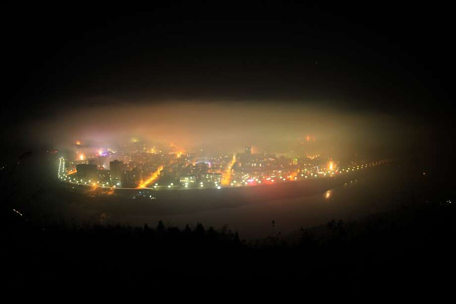 In this photo taken on 00:13 a.m. on Sunday, Feb. 10, 2013, smog covers the downtown area of Zhushan County, central China's Hubei Province, after residents around the area set off fireworks to celebrate the arrival of Chinese Lunar New Year. Setting off fireworks is a tradition in China during the Spring Festival, which result in air pollution in varying degrees, Xinhua said. Photo: Zhang Lei, Associated Press
