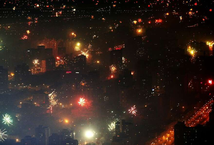 In this photo released by China's Xinhua News Agency, fireworks blast on the street corners in Beiji