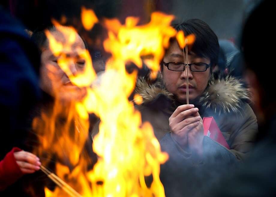 A Chinese man prays for health and fortune on the first day of the Lunar New Year at Yonghegong Lama Temple in Beijing Sunday, Feb. 10, 2013. Millions across China are celebrating the arrival of the Lunar New Year, the Year of the Snake, marked with a week-long Spring Festival holiday. Photo: Andy Wong, Associated Press