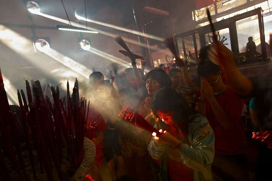 Indonesians of Chinese descent pray in the smoke filled Vihara Dharma Bhakti temple on the first day of the Chinese Lunar New year February 10, 2013 in Jakarta, Indonesia.  Chinese people around the world are ushering in the Year of the Snake with prayers, feasts and fireworks. Photo: Ed Wray, Getty Images