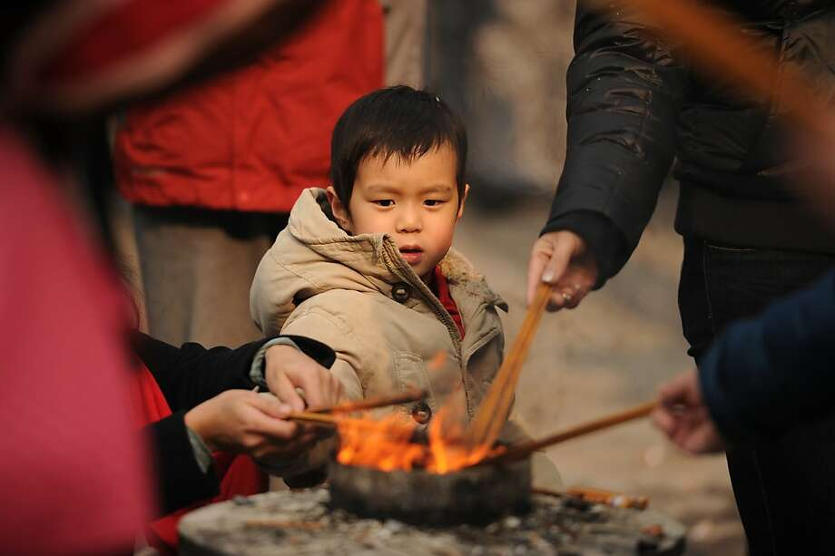 A child watches joss sticks burn to pray in the Jing An temple in Shanghai as a billion-plus Asians ushered in the Year of the Snake on February 10, 2013. From Australia to South Korea, millions of people travelled huge distances to reunite with their families for Lunar New Year -- the most important holiday of the year for many in Asia -- indulging in feasts and celebrations. Photo: Peter Parks, AFP/Getty Images