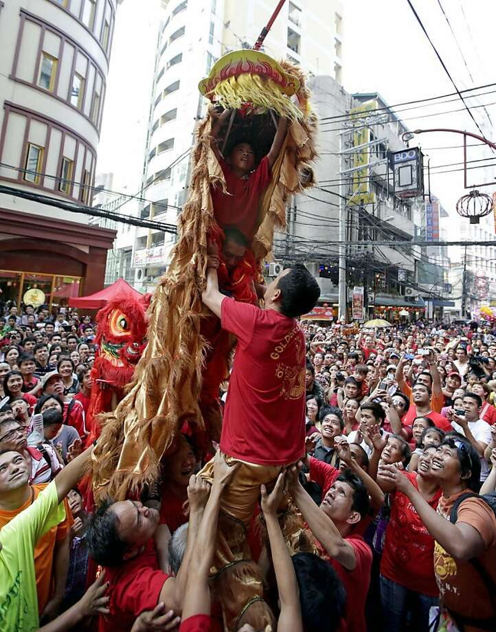 Lion dancers reach out for a cash gift dangled by a Chinese-owned business establishment in celebration of Chinese New Year Sunday, Feb. 10, 2013  at Chinatown district of Binondo in Manila, Philippines. This year marks the Year of the Snake in the Chinese calendar. Photo: Bullit Marquez, Associated Press