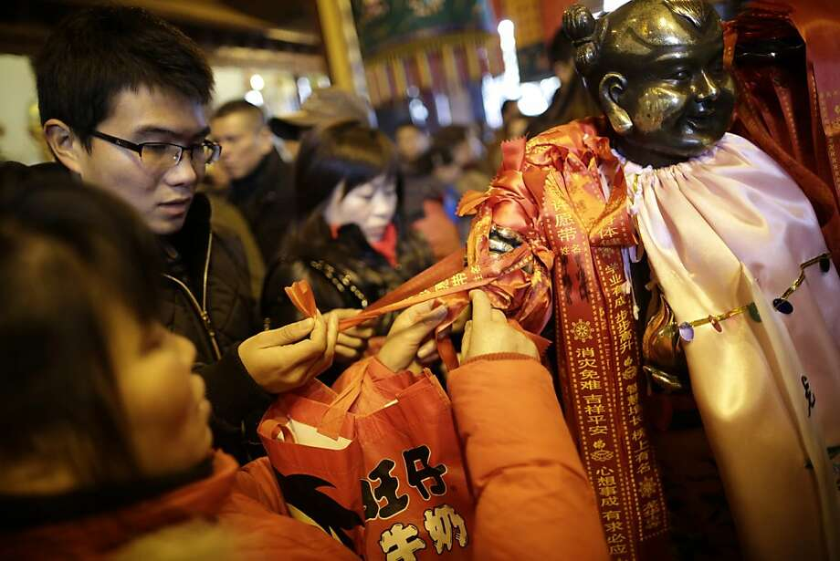 People tie wish ribbons to a statue of a god at Longhua Temple on the first day of the Lunar New Year in Shanghai, China on Sunday, Feb. 10, 2013.  Millions across China are celebrating the arrival of the Lunar New Year, the Year of the Snake, marked with a week-long Spring Festival holiday. Photo: Eugene Hoshiko, Associated Press