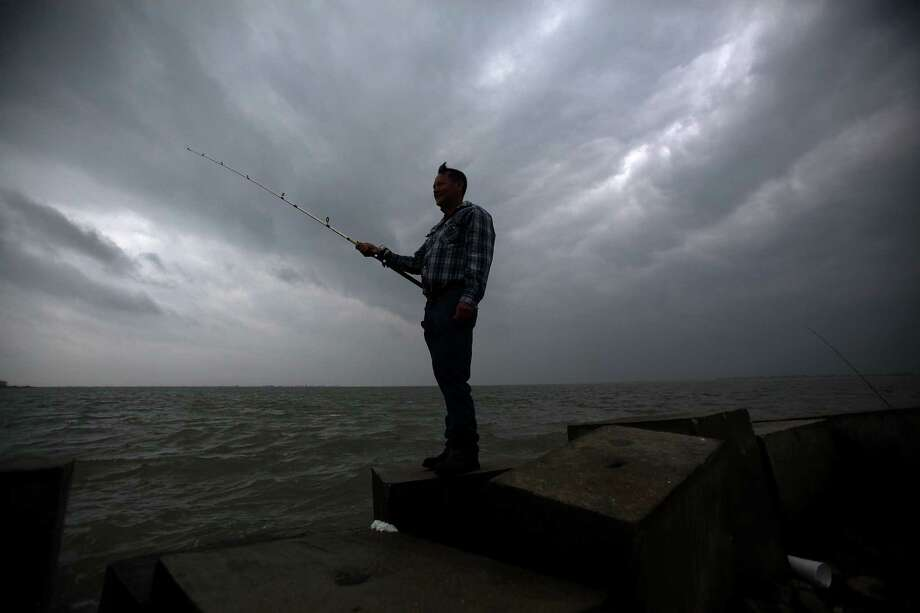 Alfides Arana, 58, of Galveston, is fishing in the West Bay as a light rain moves into the area on Sunday, Feb. 10, 2013, in Galveston. Photo: Mayra Beltran, Houston Chronicle / © 2013 Houston Chronicle