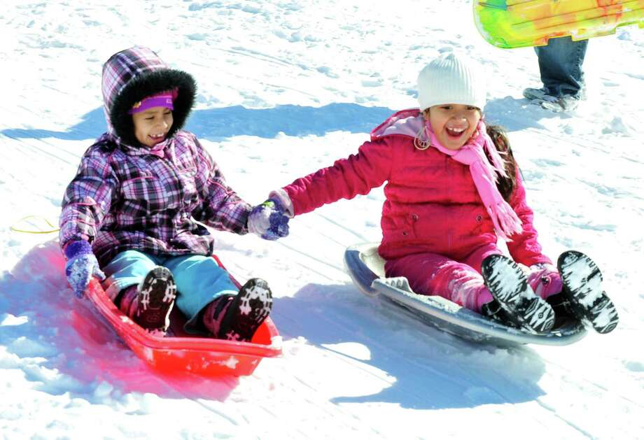 Daisy Salazar, left, and her friend, Gina Panez, both 7, sled together at Broadview Middle School in Danbury, Sunday, Feb. 10, 2013. Photo: Michael Duffy / The News-Times