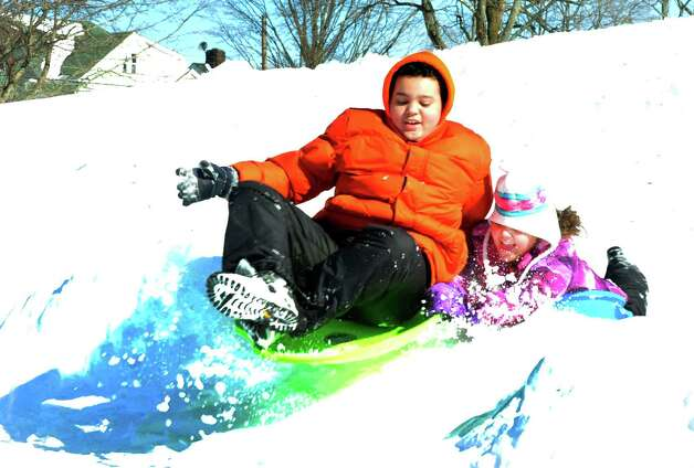 Elijah Wilson, 14, and his sister, Alexandria, 10, go over a jump while sledding  at Broadview Middle School in Danbury, Sunday, Feb. 10, 2013. Photo: Michael Duffy / The News-Times