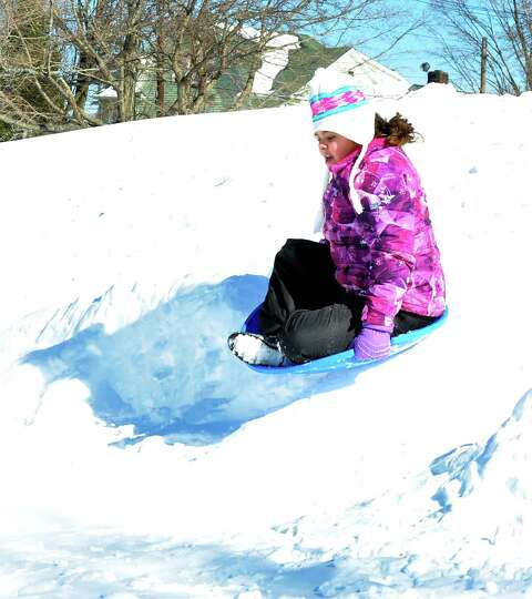 Alexandria Wilson, 10, goes over a jump while sledding  at Broadview Middle School in Danbury, Sunda