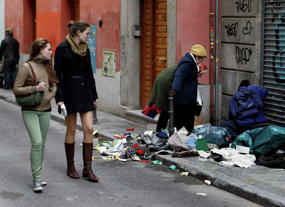 Young women look on as people sort through garbage on the sidewalk after a Sunday street market in Madrid, Spain, on Sunday. On Wednesday, demonstrators protested against cutbacks in education. Tens of thousands of people across Spain protested the cuts as the country slides into recession, with the eurozone's highest unemployment rate and more than half of Spaniards under 25 years old jobless. Photo: AP