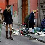 Young women look on as people sort through garbage on the sidewalk after a Sunday street market in Madrid, Spain, on Sunday. On Wednesday, demonstrators protested against cutbacks in education. Tens of thousands of people across Spain protested the cuts as the country slides into recession, with the eurozone's highest unemployment rate and more than half of Spaniards under 25 years old jobless.