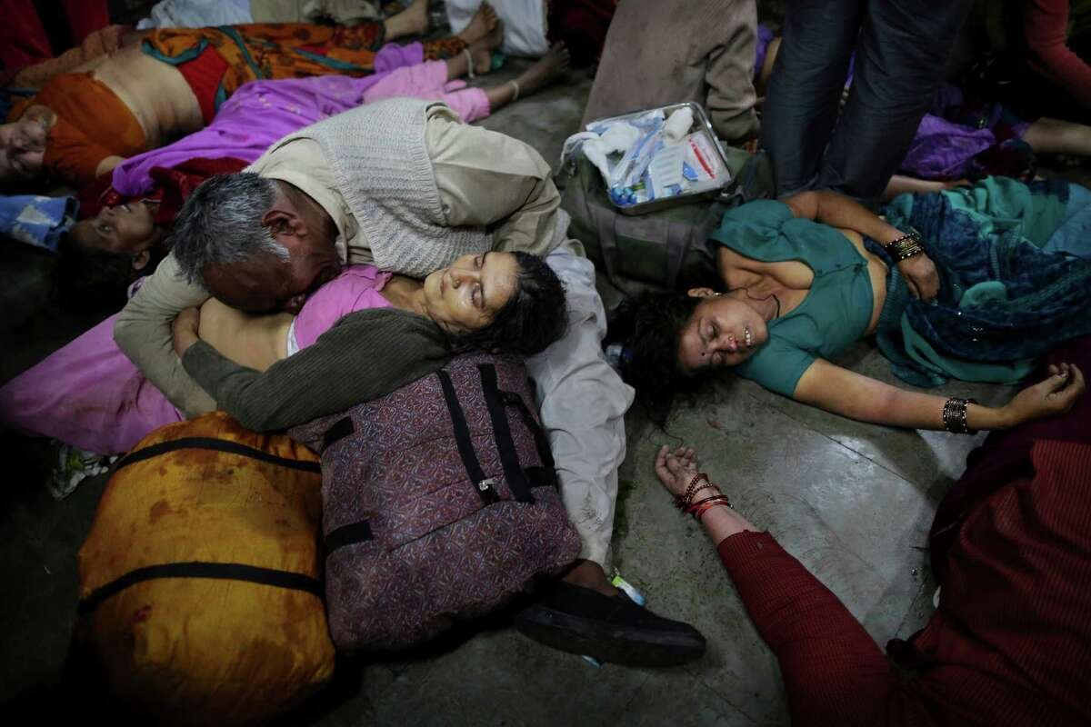 An Indian man weeps as he holds his wife who was killed in a stampede on a railway platform as other bodies are seen beside at the main railway station in Allahabad, India, Sunday. At least ten Hindu pilgrims attending the Kumbh Mela were killed and more then thirty were injured in a stampede on an overcrowded staircase, according to Railway Ministry sources.