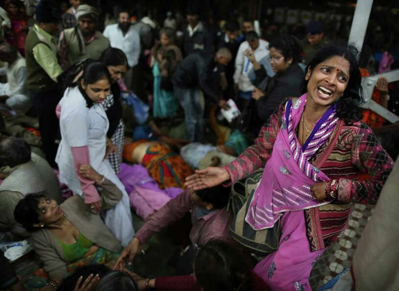 An Indian woman weeps as she and other family members mourn next to the body of a relative who was k