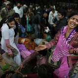 An Indian woman weeps as she and other family members mourn next to the body of a relative who was killed in a stampede on a railway platform at the main railway station in Allahabad, India, Sunday.