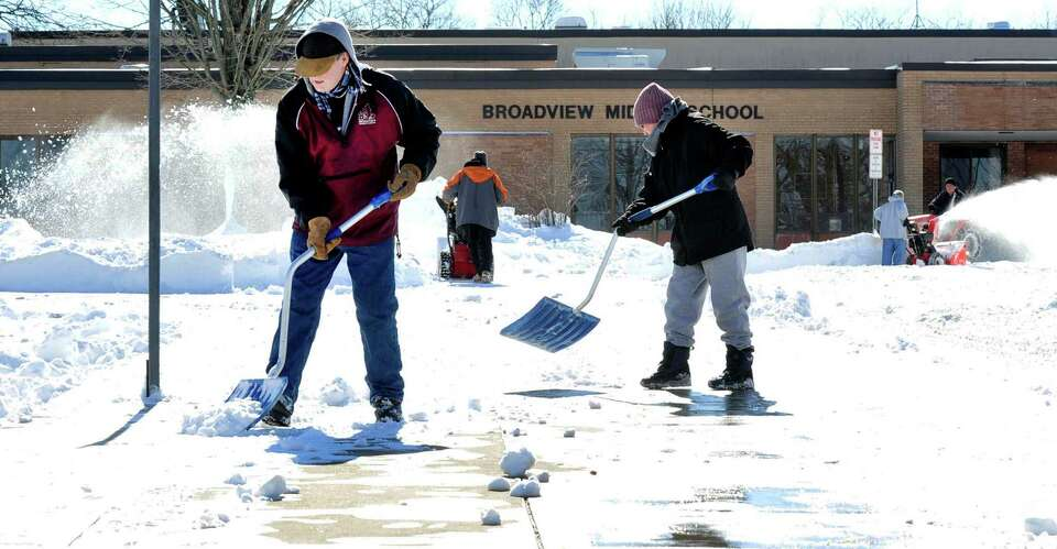 Workers clear snow outside Broadview Middle School  in Danbury, Sunday, Feb. 10, 2013.