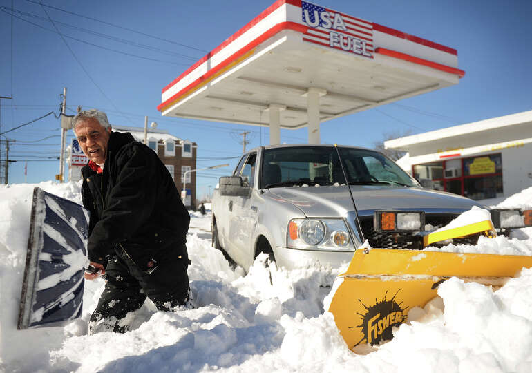 USA Fuel owner Fayez Ghaly shovels out his truck after becoming stuck in the deep snow while plowing