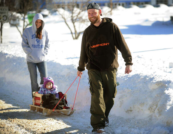 Their street still unplowed, Matt and Kim Lanier and their daughter Jenna, 16 months, head out on foot on the Boston Post Road in Milford, Conn. on Sunday, February 10, 2013. Photo: Brian A. Pounds / Connecticut Post