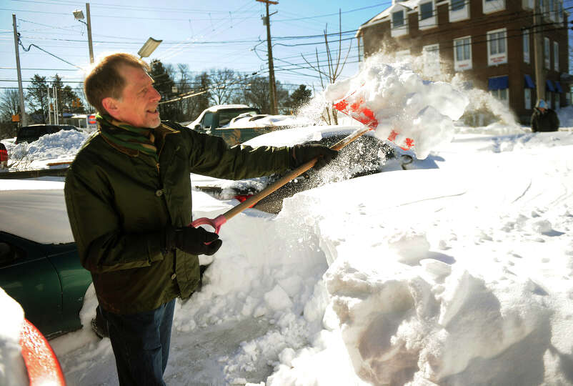 Bob Davis of Milford shovels over three feet of snow from his driveway on High Street in Milford, Co