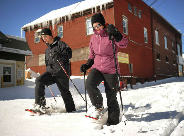 Their street still unplowed, Marc and Michelle Zahariades use snowshoes to travel down Factory Lane in Milford, Conn. on Sunday, February 10, 2013. Photo: Brian A. Pounds / Connecticut Post