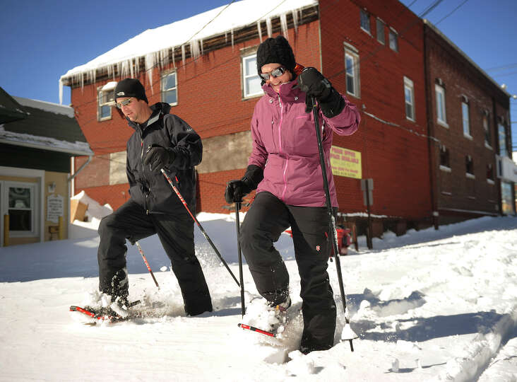 Their street still unplowed, Marc and Michelle Zahariades use snowshoes to travel down Factory Lane