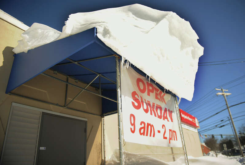 An overhang of snow appears ready to avalanche on the awning of a Boston Post Road business in Milfo