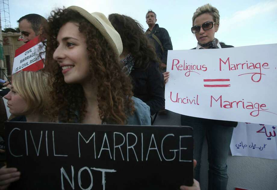 Lebanese women hold placards as they attend a protest demanding a law that guarantees any Lebanese citizen the right to a civil marriage in Beirut, Lebanon, Monday. Photo: AP