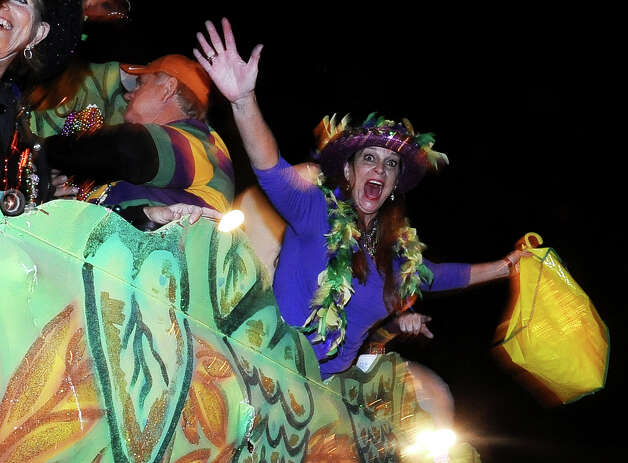 Marianne Petry throws beads from the Beer Meister float as they parade down Proctor Street in Port Arthur during the Total Krewe of Aurora Parade on Saturday, February 9, 2013. Photo taken: Randy Edwards/The Enterprise