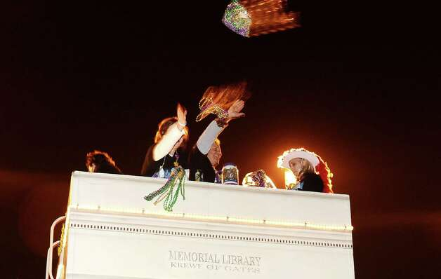 The Memorial Library Krewe of Gates members throw beads to a ecstatic crowd down Proctor Street in Port Arthur during the Total Krewe of Aurora Parade on Saturday, February 9, 2013. Photo taken: Randy Edwards/The Enterprise Photo: Randy Edwards