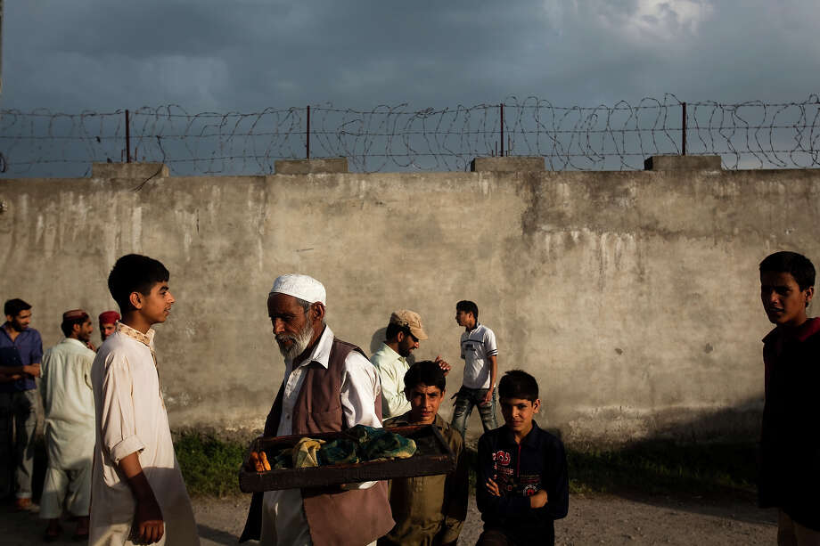 An elderly man sells pastries to a gathering crowd of onlookers outside the compound where Osama Bin Laden was killed in an operation by US Navy Seals, on May 4, 2011, in Abottabad, Pakistan. Bin Laden was killed during a U.S. military mission on May 2, at the compound. The Obama administration have decided not to release photographs of Bin Laden's body. Photo: Warrick Page, Getty Images / 2011 Warrick Page