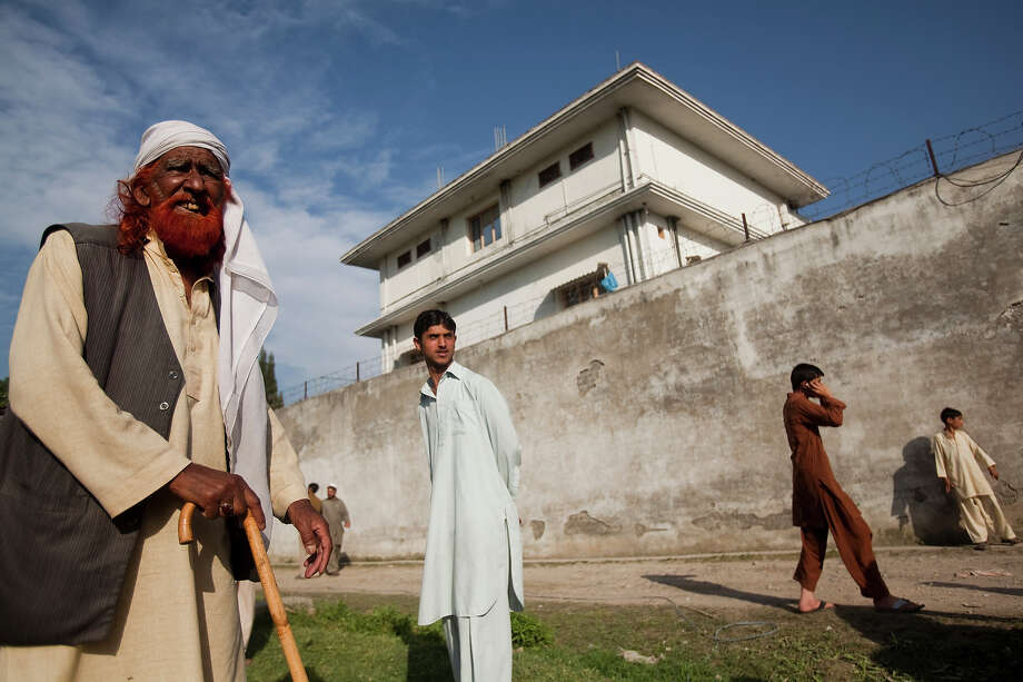 Locals gather outside the compound where Osama Bin Laden was reportedly killed in an operation by US Navy Seals, on May 3, 2011, in Abottabad, Pakistan. Bin Laden was killed during a U.S. military mission on May 2, at the compound. The Obama administration have decided not to release photographs of Bin Laden's body. Photo: Warrick Page, Getty Images / 2011 Warrick Page