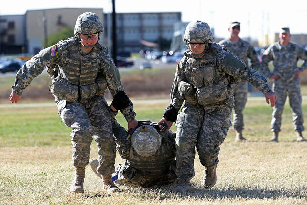 Pvt. Alexandra Zierke, 18 (left), of North Liberty, Iowa, and Pfc. Justine Westbrook, 18, of Seattle drag a soldier to safety as part of their training. Photo: Jerry Lara, San Antonio Express-News / San Antonio Express-News