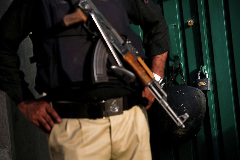 A Pakistani policeman stands next to the locked entrance to the compound where Osama Bin Laden was killed in an operation by US Navy Seals, on May 4, 2011, in Abottabad, Pakistan. Bin Laden was killed during a U.S. military mission on May 2, at the compound. The Obama administration have decided not to release photographs of Bin Laden's body. Photo: Warrick Page, Getty Images / 2011 Warrick Page